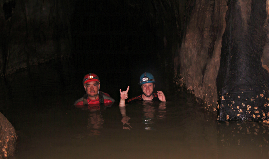 Jud Partin shows the 'hook em horns' sign in a cave in the Philippines