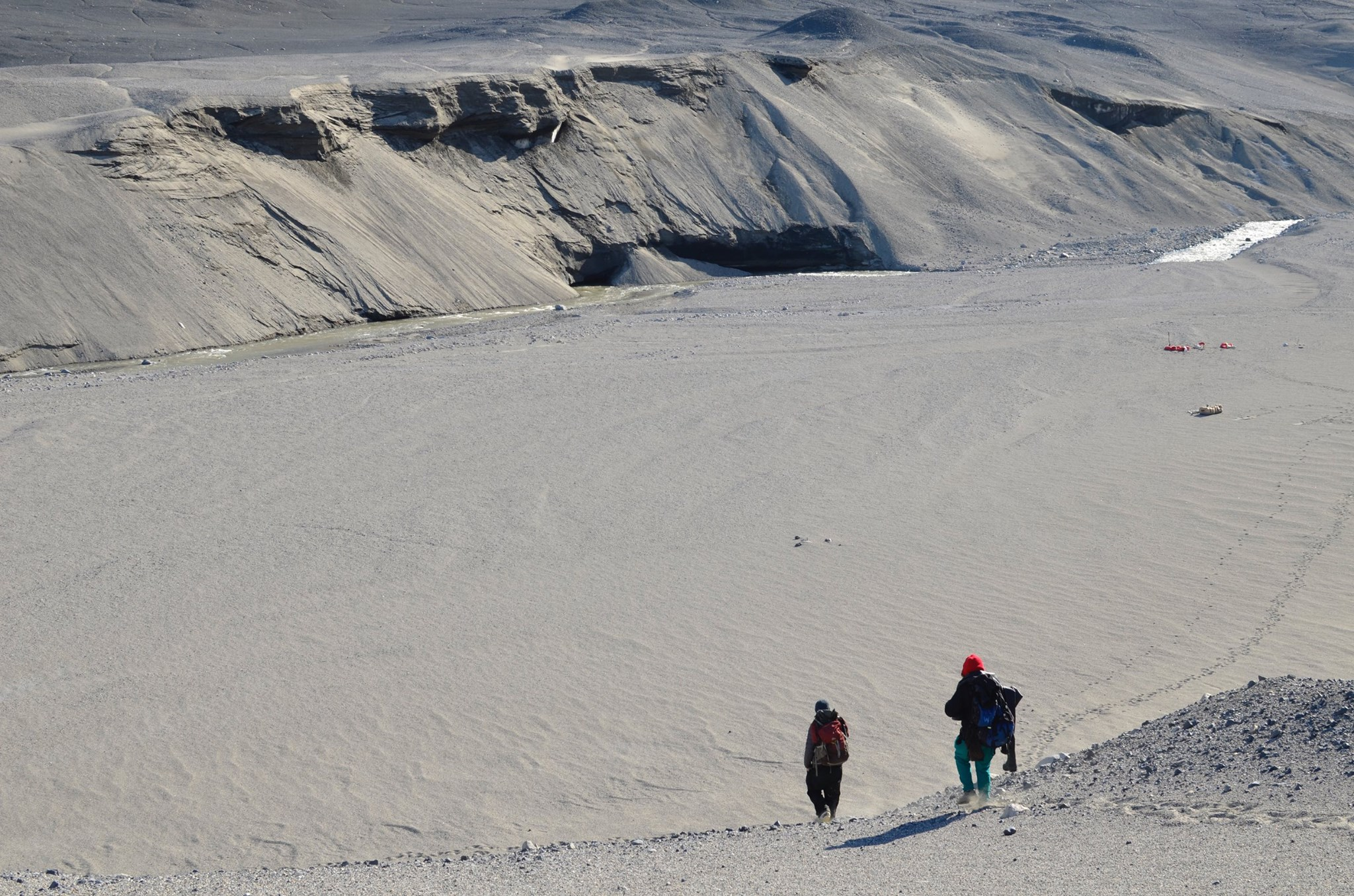 Jackie Watters and Stephen Chignell descending into the Garwood River floodplain to investigate the recently re-exposed massive ice cliff in Garwood Valley. The cliff is a dramatic example of rapid buried ice loss observed in the Dry Valleys region. (Photo by Logan Schmidt)