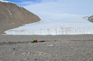 Joseph Levy and Jackie Watters collect soil measurements from within a water track (zone of enhanced soil moisture) in Taylor Valley. These measurements will help characterize the geologic controls on the existence and location of shallow groundwater in Antarctica's Dry Valleys, important for determining which areas of the valleys are stable. Howard Glacier is seen in the background. (Photo by Logan Schmidt)
