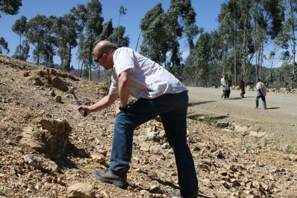 Field photo showing Thorsten Becker hitting a rock with a hammer.