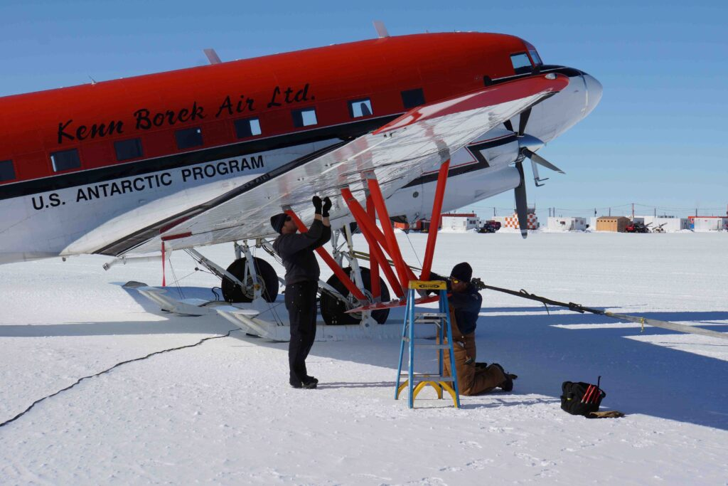 Picture showing a propeller plane parked on ice, with engineers working under the wing